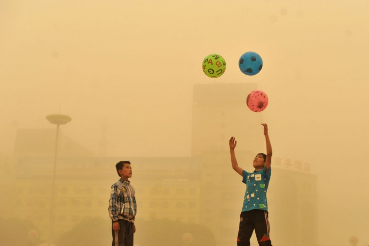 A boy watches as another boy play with balls, during a sandstorm in Kashgar city in northwestern China's Xinjiang Uighur Autonomous Region, Sunday, May 10, 2015. (Chinatopix Via AP)