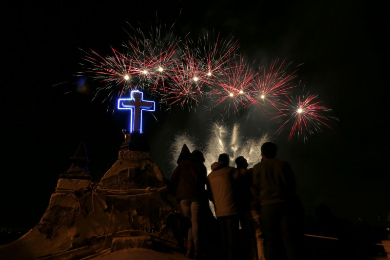 "A group of people stand on top of the Santa Maria Magdalena Church while watching fireworks, Sunday, May 10, 2015, in Tepexpan, Mexico. Tepexpan is closing out its annual two-week celebration honoring ""El Senor de Gracias,"" the town's patron saint. (AP Photo/Julio Cortez)"