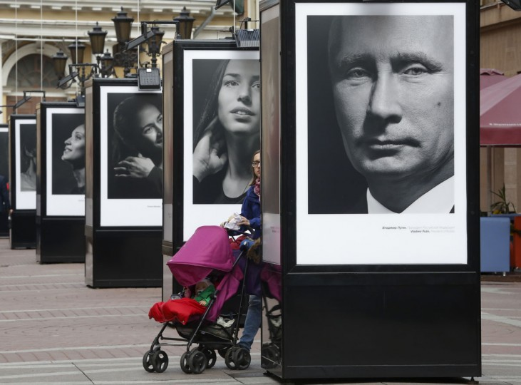 A woman walks past a portrait of Russian President Vladimir Putin displayed among portraits of Russian athletes, winners of the Sochi 2014 Winter Olympics at the photo exhibition 'Country of the victory. The victory of the country' in St.Petersburg, Russia, Thursday, May 28, 2015. (AP Photo/Dmitry Lovetsky)
