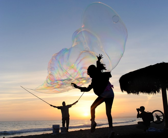 Frenchy Monceaux entertains at the base of the San Clemente Pier with a giant bubble show on Tuesday, May 12, 2015 in San Clemente, Calif. (Ana Venegas/The Orange County Register via AP)