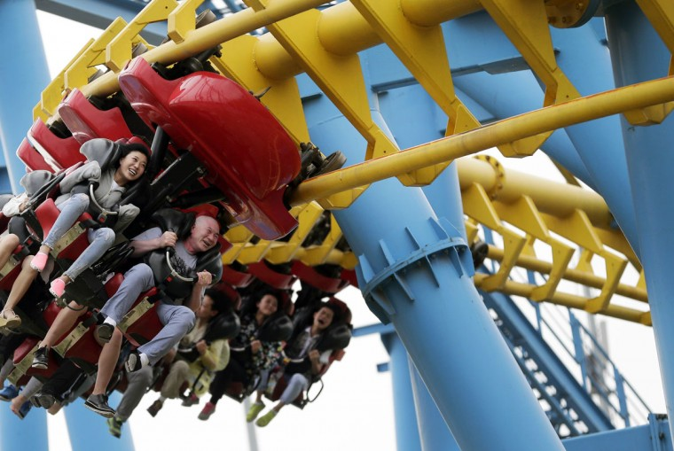People ride a roller-coaster at Xiedao's theme park during a May Day holiday in Beijing, China, Friday, May 1, 2015. Millions of Chinese are taking advantage of the May Day holidays to visit popular tourist sites. (AP Photo/Andy Wong)