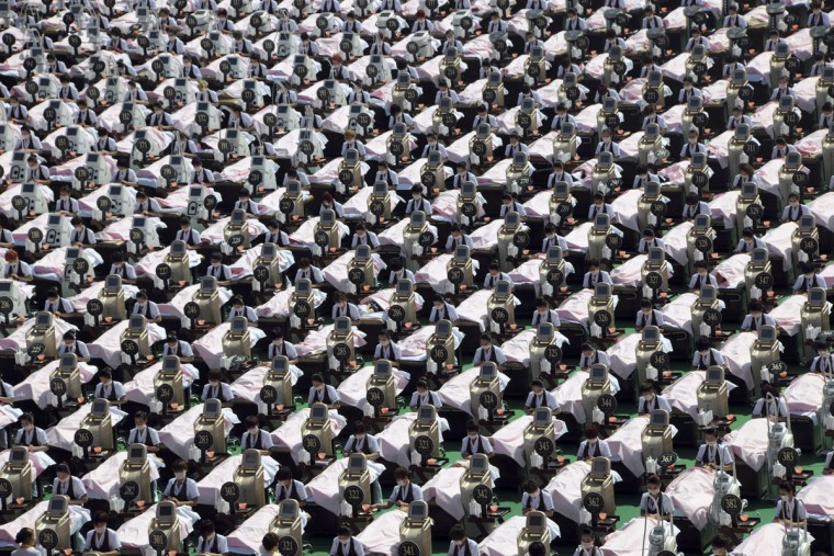 One thousand cosmetologists from a Chinese beauty salon group perform skin care on 1,000 women at a stadium in an attempt to set a new Guinness World Record in Jinan city in east China's Shandong province Monday, May 4, 2015. The last record was for 100 cosmetologists. (Chinatopix via AP)