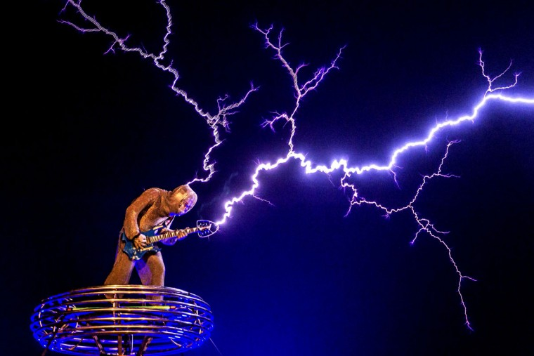 In this Wednesday, April 29, 2015 photo, guitarist Wang Hongbin wearing an iron mesh suit performs along with man-made lightning created by his uncle Wang Zengxiang during a show in a village in Changle city in southeast China's Fujian province. Wang Zengxiang, a former electronics engineer, who made lightning equipments using the Tesla coil, a high-frequency air-core transmitter, after quitting his job in 2012, has started the music band Lei Ting Feng, or Lightning Craze, and has appeared in popular TV shows. (Chinatopix via AP)