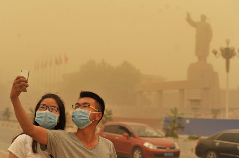 A couple wears facemarks as they pose for a self-portrait near a large statue of late Chinese leader Mao Zedong during a sandstorm in Kashgar city in northwestern China's Xinjiang Uighur Autonomous Region, Sunday May 10, 2015. (Chinatopix Via AP)