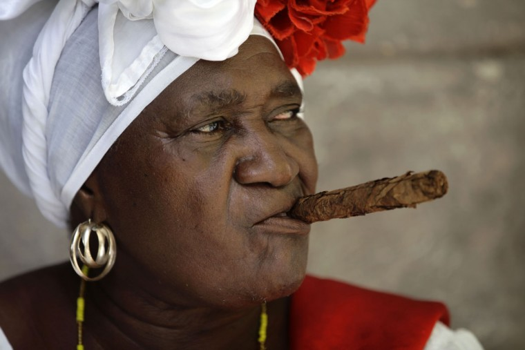 Street entertainer and fortune teller®Juana La Cubana® holds a cigar in her mouth as she waits for tourists in Havana, Cuba, Sunday, May 24, 2015. Juana is 72 years old and has worked in the Cathedral square in Old Havana for 28 years. (AP Photo/Desmond Boylan)