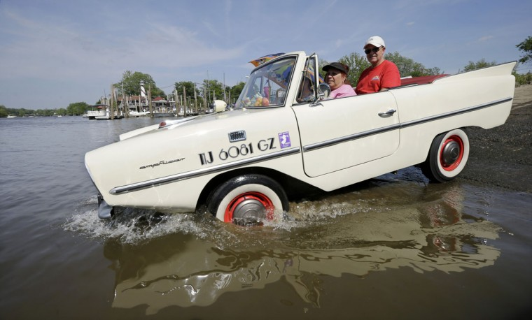 With friend Lisa Schlosser, of Browns Mills, N.J., and husband, Bob Cabanas, aboard, Ina Cabanas of Pemberton Borough, N.J. drives her 1967 Amphicar down a boat ramp into the Delaware River Monday, May 25, 2015, in Burlington City, N.J. The car was designed and constructed to also be water-going. (AP Photo/Mel Evans)