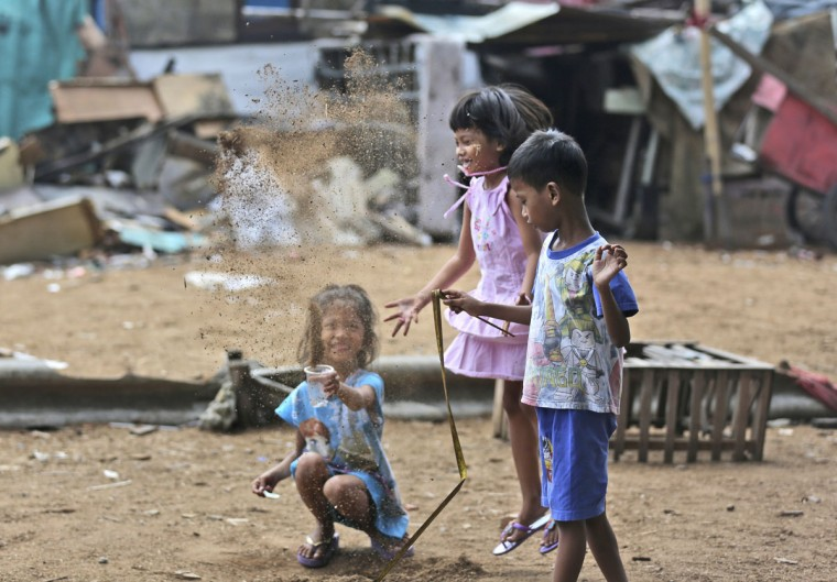 Indonesian children throw dust into the air as they play near their houses at a slum in Jakarta, Indonesia Tuesday, May 12, 2015. (AP Photo/Tatan Syuflana)