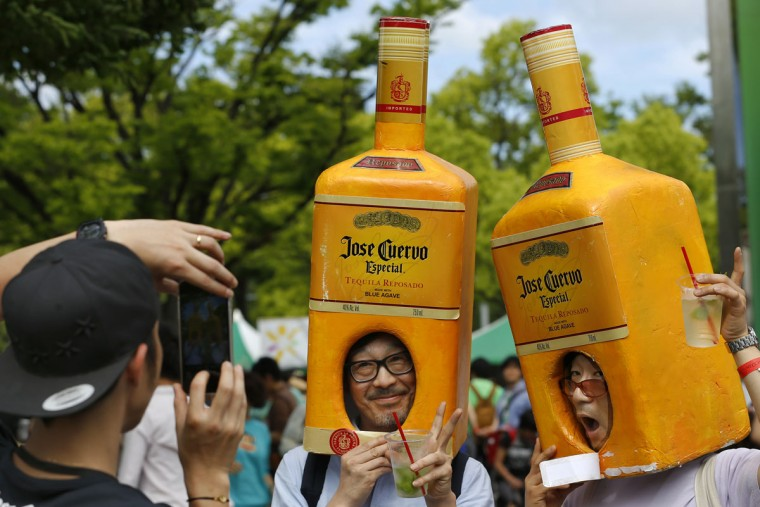 Men wearing the liquor bottle-shaped decoration pose for a photo during a local festival at a Tokyo park, Monday, May 4, 2015. (AP Photo/Shizuo Kambayashi)