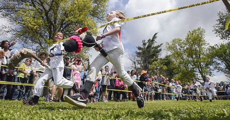 Stick horse jockeys Darrius Young, left, and Olivia Bodner cross the finish line during the Kid'tucky Derby, Friday May 1, 2015, at Jennie Rogers Elementary School in Danville, Ky. The school during the week talked about the history of the Kentucky Derby. (Clay Jackson/The Advocate-Messenger via AP)