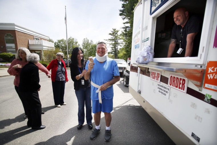 With child-like joy, resident Ben Kohn receives his ice cream cone from the Krispy Cone ice cream truck at Mt. Greylock Extended Care Facility Friday, May 15, 2015, in Pittsfield, Mass. The Krispy Cone ice cream truck provided residents with cool treats at the facility. (Stephanie Zollshan/The Berkshire Eagle via AP)
