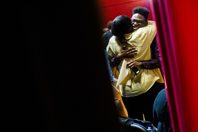 Sandrese Green, facing, hugs Regina Broomfield, Mott Community College admissions supervisor, after announcing he plans to attend Marygrove College, during the Urban Center for Post-Secondary Access and Success' College Decision Day celebration Friday, May 15, 2015, at Coates Auditorium in Beecher, Mich. (Jake May/The Flint Journal-MLive.com via AP)