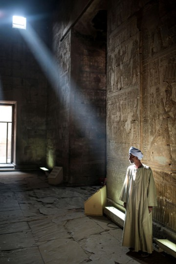 A tour guide waits for tourists inside inside the ancient Temple of Edfu, considered one of the best preserved Egyptian temples, which was built around 3000 years ago, near Aswan, southern Egypt, Friday, May 1, 2015. (AP Photo/Mosa'ab Elshamy)