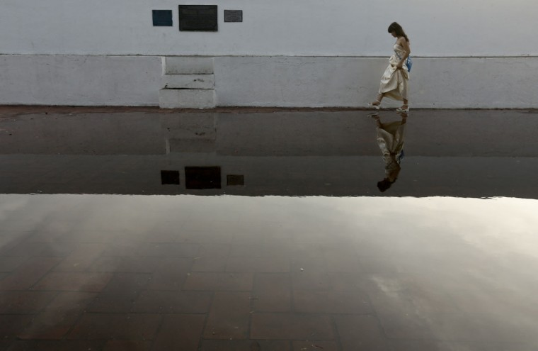 A girl tries not to get her feet wet in a puddle while she walks after an afternoon rain shower at Plaza de Francia in the Casco Viejo neighborhood of Panama City, Wednesday, May 27, 2015. (AP Photo/Arnulfo Franco)