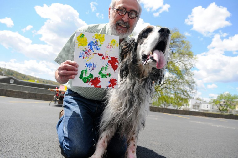 Robert Stickloon holds up the art work made by his pet Jesse at the Paw-Casso: Art by Dogs event at The Walk In Art Center in Schuylkill Haven, Pa. Saturday, May 2, 2015. Donations benefited Hillside SPCA in Pottsville, Pa. (Jacqueline Dormer/Republican-Herald via AP)