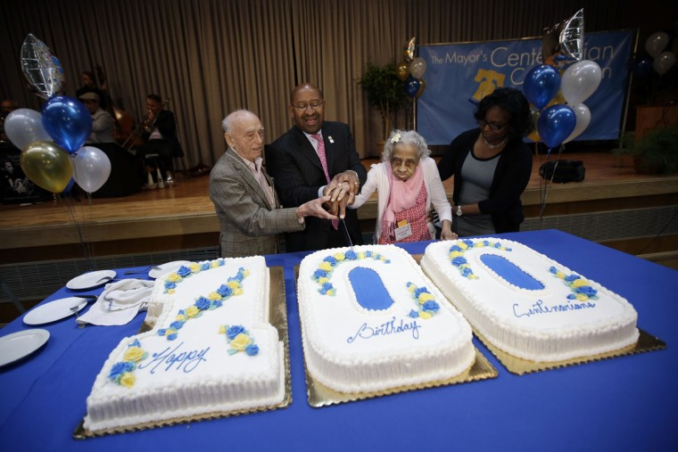 Dr. Eli Zebooker, left, who was born on April 4, 1913, Mayor Michael Nutter, Fannie Mae Ausby, who was born on May 9, 1907, and Ausby's grand-daughter, Laura Hammond, cut a cake during Philadelphia's 15th Annual Centenarian Celebration at a union hall on Thursday, May 21, 2015, in Philadelphia. The city established the event honoring its 100-year-old residents in 2001 to mark the anniversary of the completion of the historic century-old City Hall. (AP Photo/Matt Slocum)