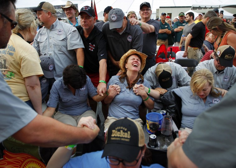 Members of the Sweet Swine of Mine Team gather in prayer as they wait for the announcement of their second place in shoulder competition at the Memphis In May World Championship Barbecue Cooking Contest at Tom Lee Park Saturday evening, Saturday, May 16, 2015 in Memphis. (Jim Weber/The Commercial Appeal via AP)