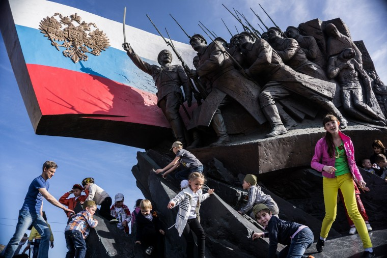 Children play on the Memorial to the Heroes of World War I in Victory Park during celebrations marking the 70th anniversary of Nazi Germany's defeat and the end of World War II in Moscow. Celebrations are taking place throughout the day across the city. Most European leaders have snubbed the parade because they accuse Russia of actively interfering the war in eastern Ukraine. (Alexander Aksakov/Getty Images)