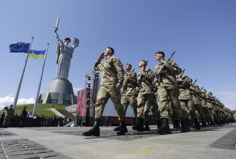 Ukrainian soldiers march in front of the Motherland Monument in Kiev on May 9, 2015 during a ceremony marking the 70th anniversary of the end of WWII. Tanks and rocket systems rolled through the rebel bastion of Donetsk in east Ukraine on May 9 as pro-Russian insurgents feted 70 years since victory over Nazi Germany in WWII. Imitating a vast military parade being held simultaneously in Moscow, some 1,500 separatist fighters marched through the rebel-held city clutching red Soviet flags and several portraits of Stalin. (Anatolii Stepanov/AFP-Getty Images)