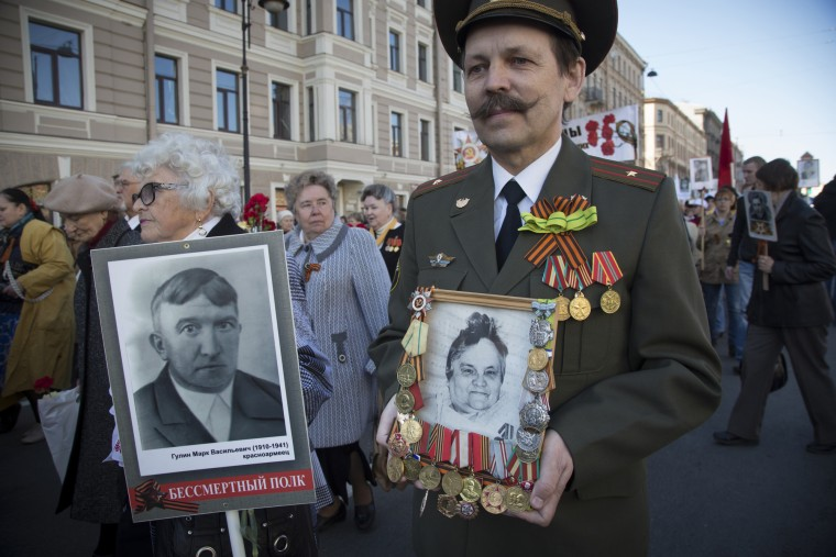 Viktor Lukyanov, right, carries a portrait and medals of his mother Valentina Lukyanova, a participant in World War II during 70th anniversary celebrations of the defeat of the Nazis in World War II. About 100,000 people walked the St. Petersburg, Russia, streets in a march named 'Immortal regiment' while carrying portraits their relatives who fought in the war. (Dmitry Lovetsky/Associated Press)