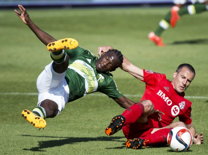 Toronto FC midfielder Benoit Cheyrou, right, battles for the ball against Portland Timbers midfielder Diego Chara during the first half of an MLS soccer game in Toronto. (Nathan Denette/The Canadian Press via AP)