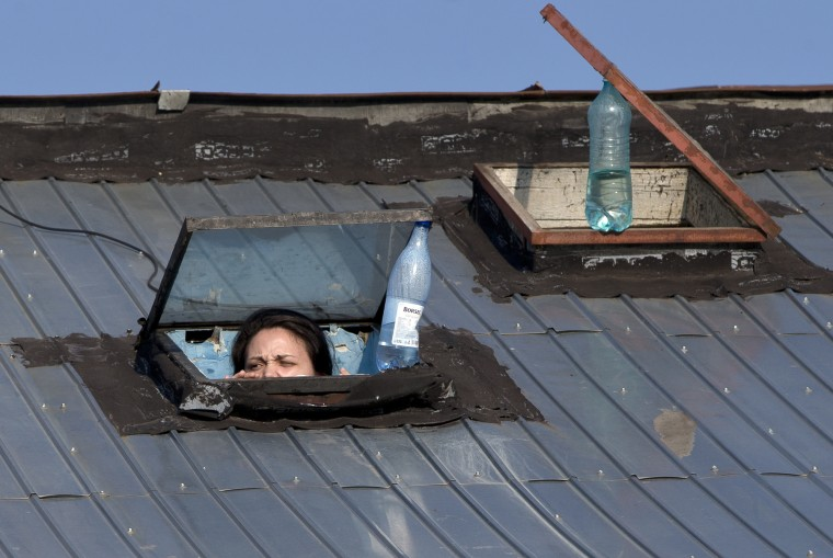 A woman peers through a roof window to watch a protest march against illegal logging in Bucharest, Romania. Thousands have protested what they say is the illegal mass cutting of forests in Romania, blaming politicians for allowing the deforestation of some of the most important woodlands in Europe. (Vadim Ghirda/Associated Press)