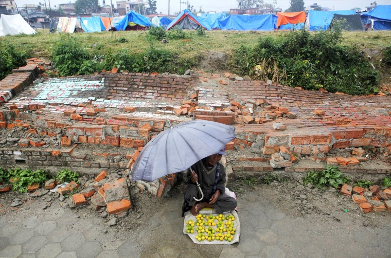 A Nepalese street vendor, waiting for customers in front of a fallen brick wall, sits near makeshift tents for those whose houses were damaged by the earthquake in Kathmandu, Nepal. The international response has been slow to an appeal for emergency funds to help the millions of people hit by last month's earthquake in Nepal, a U.N. official said. (Niranjan Shrestha/Associated Press)