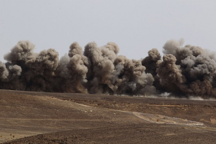 "Smoke rises following an airstrike by a U.S. strategic bomber during 18-nation military exercises in a field near the border with Saudi Arabia, in Mudawara, 280 kilometers (174 miles) south of Amman, Jordan, Monday, May 18, 2015. Some 10,000 troops took part in the two-week ""Eager Lion"" exercises hosted by Jordan for the fifth year. (AP Photo/Raad Adayleh)"