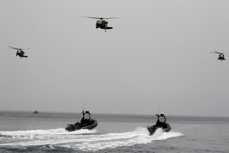 Jordanian forces practice a drill to free a ship seized by mock terrorists during 18-nation military exercises off Aqaba's seaport, 330 kilometers (205 miles) south of Amman, Jordan, Monday, May 18, 2015. (AP Photo/Raad Adayleh)