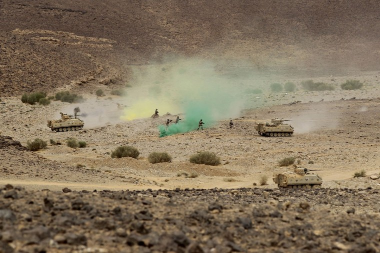 "Jordanian soldiers along with tanks participate in 18-nation military exercises in a field near the border with Saudi Arabia, in Mudawara, 280 kilometers (174 miles) south of Amman, Jordan, Monday, May 18, 2015. Some 10,000 troops took part in the two-week ""Eager Lion"" exercises hosted by Jordan for the fifth year. (AP Photo/Raad Adayleh)"