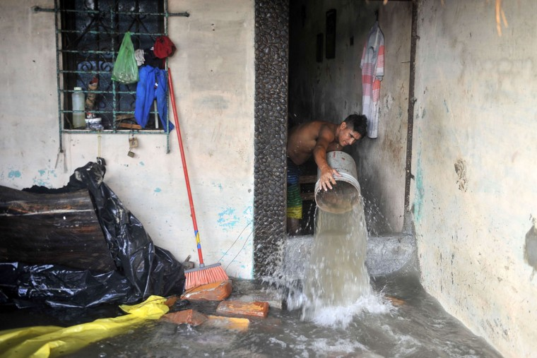 A man removes the water from his home in an area flooded due to a strong ocean swell in La Libertad, 34 km south of San Salvador, on May 3, 2015. (Marvin RECINOS/AFP/Getty Images)