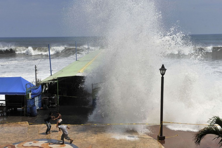 People try to protect themselves from the waves in La Libertad, 34 km south of San Salvador, on May 3, 2015. (Marvin RECINOS/AFP/Getty Images)