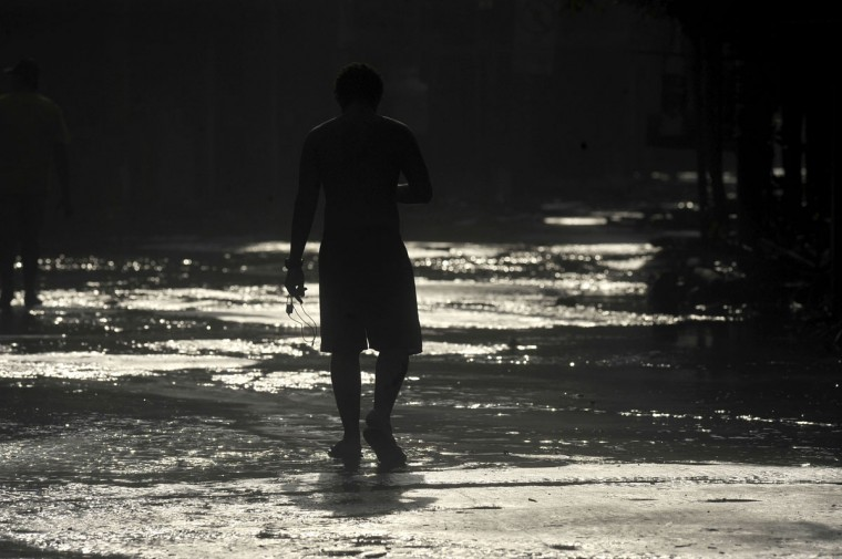 A man walks along an area affected by a strong ocean swell in La Libertad, 34 km south of San Salvador, on May 3, 2015. (Marvin RECINOS/AFP/Getty Images)