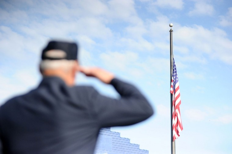 Veteran Al Santelli, of Mount Carmel, salutes the American flag as it is lowered to half-staff during a Memorial Day service at Second and Oak streets in Mount Carmel, Pa., Monday, May 25, 2015. A parade through the community was held after the service. (Larry Deklinski/The News-Item via AP)