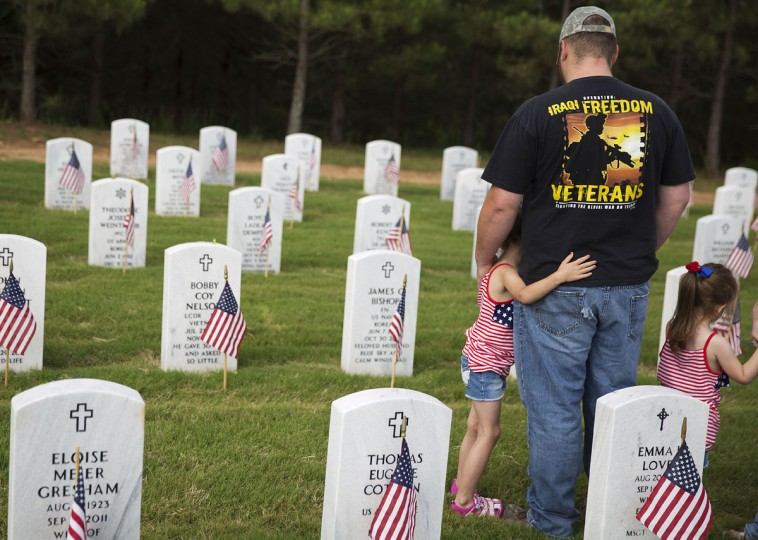 Iraq War veteran, retired Pvt. Rocky Bishop is embraced by his daughter Cyndney, 6, while visiting the grave of his grandfather, Korean War veteran James Bishop, with his other daughter Hannah, 4, at Georgia National Cemetery, in honor of Memorial Day, Monday, May 25, 2015, in Canton, Ga. (AP Photo/David Goldman)