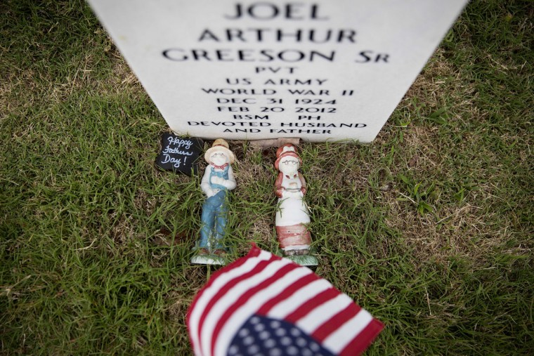 Figurines of a man and a woman lay on the grave of WWII veteran Pvt. Joel Greeson Sr., at Georgia National Cemetery on Memorial Day, Monday, May 25, 2015, in Canton, Ga. (AP Photo/David Goldman)