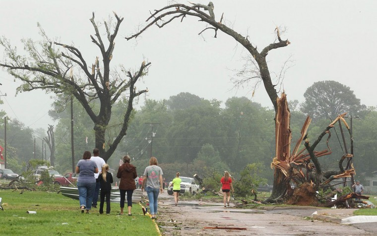 Residents survey damage near an elementary school, caused by severe weather, Monday, May 11, 2015, in Van, Texas. About 30 percent of the community was damaged from the storm late Sunday, according to Chuck Allen, fire marshal and emergency management coordinator for Van Zandt County. (AP Photo/Todd Yates)