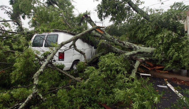 A vehicle sits damaged under downed trees from severe weather, Monday, May 11, 2015, in Van, Texas. About 30 percent of the community was damaged from the storm late Sunday, according to Chuck Allen, fire marshal and emergency management coordinator for Van Zandt County. (AP Photo/Todd Yates)