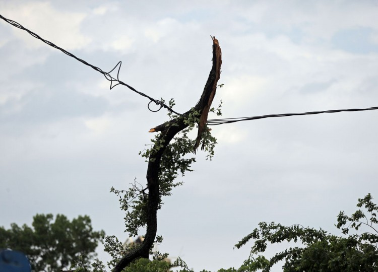 A tree hangs in power lines at the Bent Creek Estates subdivision following a storm in Denton, Texas, Sunday, May 10, 2015. Several Great Plains and Midwest states were in the path of severe weather, including in North Texas, where the National Weather Service said a likely tornado damaged roofs and trees near Denton. (G.J. McCarthy/The Dallas Morning News via AP)