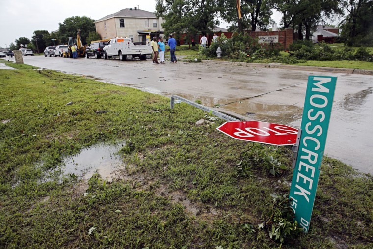 Street signs lie on the ground at the Bent Creek Estates subdivision following a storm in Denton, Texas, Sunday, May 10, 2015. Several Great Plains and Midwest states were in the path of severe weather, including in North Texas, where the National Weather Service said a likely tornado damaged roofs and trees near Denton. (G.J. McCarthy/The Dallas Morning News via AP)