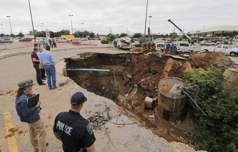 Granbury safety and public works officials deal with a sink hole that opened up after heavy rains collapsed a storm sewer under the pavement at the edge of a parking lot next to the Brookshire's store on Morgan Street in Granbury, Texas. Workers were stopping the water flow from broken pipes and rerouting water services before attempting to shore up and repair the damage, Monday, May 11, 2015. (Rodger Mallison/The Fort Worth Star-Telegram via AP)