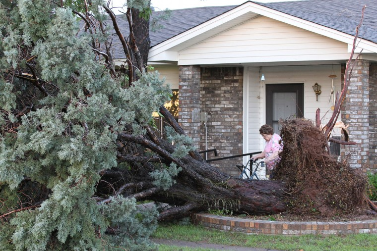 A large pine tree is uprooted in the front yard with little other damage to the home in Wichita Falls, Texas after a tornado touched down northwest of Burkburnett, Texas on Saturday night, May 9, 2015, causing damage near the intersection of Thrift Rd and Vaughn Rd. (AP Photo/Wichita Falls Times Record News, Richard Cleaver)
