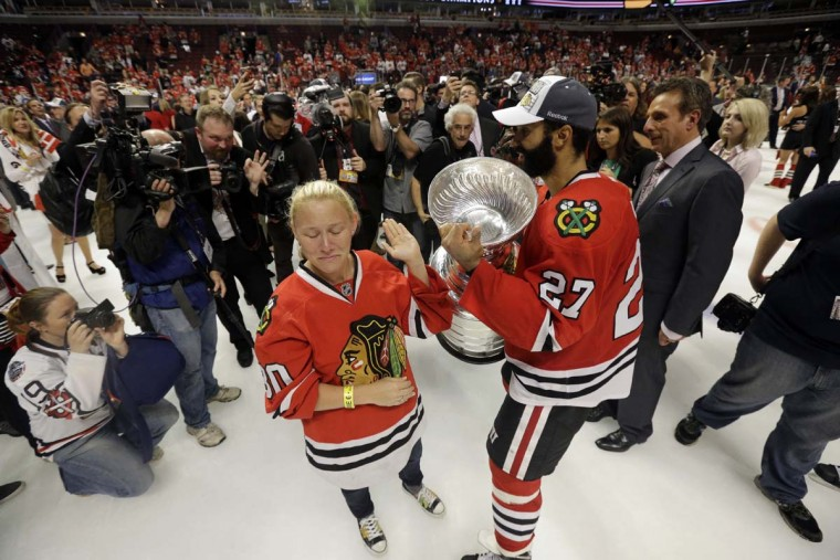Chicago Blackhawks defenseman Johnny Oduya (27) celebrates with Kelly Reif, widow of former Blackhawks equipment man Clint Reif, who died at his home in December, after defeating the Tampa Bay Lightning in Game 6 of the NHL hockey Stanley Cup Final series on Monday, June 15, 2015, in Chicago. The Blackhawks defeated the Lightning 2-0 to win the series 4-2. (AP Photo/Nam Y. Huh)