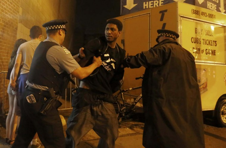 A Chicago Blackhawks fan is arrested by a Chicago police officer on Addison Street in the Wrigleyville neighborhood after the Chicago Blackhawks won the Stanley Cup, defeating the Tampa Bay Lightning Monday, June 15, 2015 in Chicago. (AP Photo/Christian K. Lee)