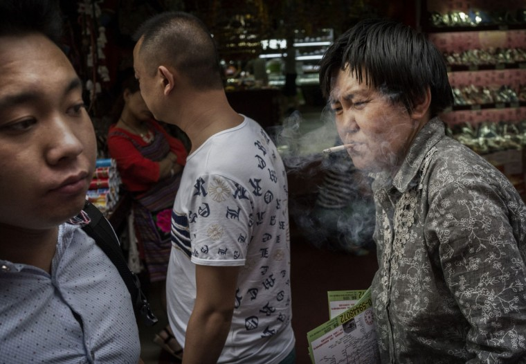 A Chinese woman smokes a cigarette in a prohibited area under tough new anti-smoking laws in a shopping market on June 1, 2015 in Beijing, China. Beijing introduced strong new measures June 1, banning smoking in many public places, in a bid to stave off a growing health crisis in the world's biggest consumer of tobacco. Past attempts have failed in China, which has more than 300 million smokers and an estimated one million smoking-related deaths each year. (Photo by Kevin Frayer/Getty Images)