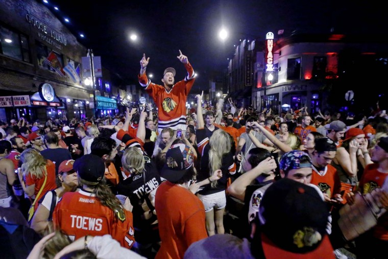 Fans celebrate the Chicago Blackhawks winning the 2015 Stanley Cup outside at Sluggers World Class Sports Bar on June 15, 2015 in Chicago, Illinois. The Blackhawks beat the Lightning 2 - 0 to win the Stanley Cup. (Photo by Jon Durr/Getty Images)