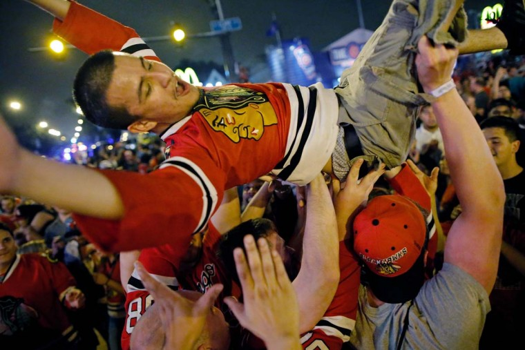 Fans celebrate the Chicago Blackhawks winning the 2015 Stanley Cup outside of Wrigley Field on June 15, 2015 in Chicago, Illinois. (Photo by Jon Durr/Getty Images)