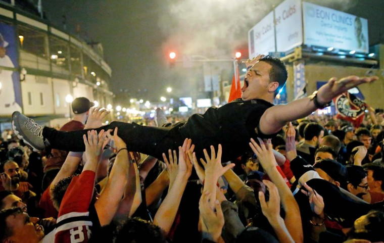 Fans celebrate the Chicago Blackhawks winning the 2015 Stanley Cup by crowd surfing at the intersection of Addison St. and Clark St. on June 15, 2015 in Chicago, Illinois. (Photo by Jon Durr/Getty Images)