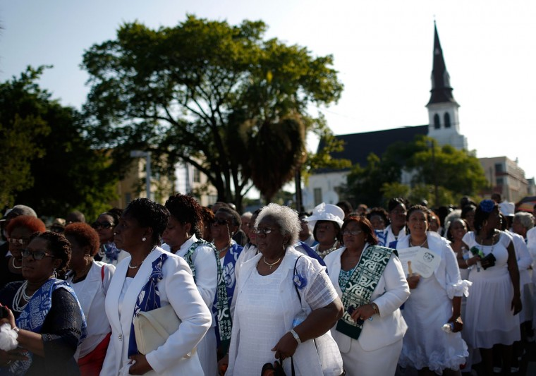 Mother Emanuel African Methodist Episcopal church is seen in the background as women dressed in white wait to enter the funeral service where U.S. President Barack Obama will deliver the eulogy for South Carolina State senator and Rev. Clementa Pinckney who was killed along with eight others in a mass shooting June 26, 2015 in Charleston, South Carolina. Suspected shooter Dylann Roof, 21, is accused of killing nine people on June 17th during a prayer meeting in the church, which is one of the nation's oldest black churches in Charleston. (Photo by Win McNamee/Getty Images)