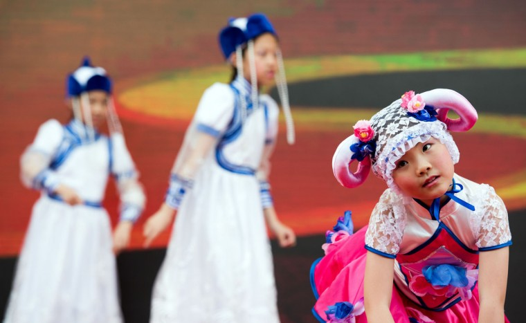Young girls dressed in Inner Mongolian costumes perform in a show during a tea promotion festival in a park in Shanghai on June 1, 2015, during International Children's Day. (AFP Photo/Johannes Eisele)