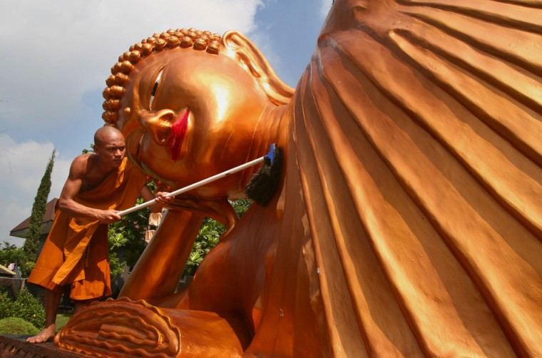 A monk cleans a huge reclining Buddha statue at a Buddhist temple in Malang in eastern Java island on June 1, 2015 on the eve of Buddha's birthday celebrated in Indonesia on June 2. Hundreds of Buddhist devotees congregate at the ancient temple of Borobudur for a religious celebration in central Java island. Buddhists are a minority in Indonesia, a predominantly Islamic country. (AFP Photo/Aman Rochman)